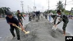 Binh sĩ Thái Lan dùng các bao tải cát để tạo thành đê chống lũ dọc theo sông Chao Phraya mà hiện chỉ cách mực nước biển hai mét