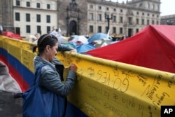 FILE - A woman writes a message to support a peace deal between the Colombian government and rebels of the Revolutionary Armed Forces of Colombia, FARC, at the main square in Bogota, Colombia, Oct. 8, 2016.