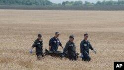 7月19日救援人员用担架抬走马航遇难者尸体
