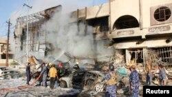 Petugas pemadam kebakaran bekerja mematikan api di lokasi serangan bom mobil di Kirkuk (23/8). (Reuters/Ako Rasheed)