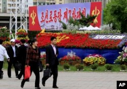 "Pedestrians walk by a flower arrangement and billboard with the words ""The 7th Congress of the Workers' Party of Korea"" in Pyongyang, North Korea, May 5, 2016."