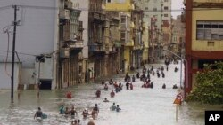 People move through flooded streets in Havana after the passage of Hurricane Irma, in Cuba, Sept. 10, 2017.