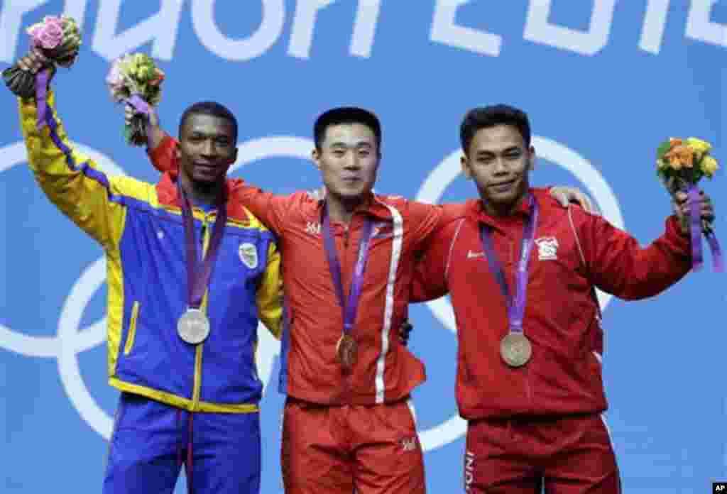 Atlet Korut, Kim Un Guk (tengah) memenangkan emas cabang angkat besi kelas 62-kilogram putera, sementara Oscar Mosquera dari Kolombia (kiri) merebut medali perak dan dan Eko Yuli Irawan dari Indonesia meraih perunggu.