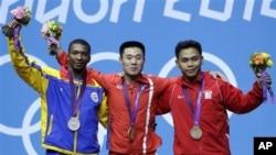 Kim Un Guk peraih medali emas dari Korea Utara (tengah) berpose bersama peraih perak, Oscar Mosquera dari Kolombia (kiri) dan peraih perunggu Eko Yuli Irawan dari Indonesia (kanan) usai penyerahan medali (30/7).