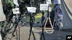 "Hanging ropes with names in Arabic for officials from the ousted regime - ""Zusan, Jamal Mubarak, Ahmed Ezz, Habib al-Adly and Hosni Mubarak"" - are seen at the protest camp in Tahrir square, Cairo, Egypt, July 26, 2011"