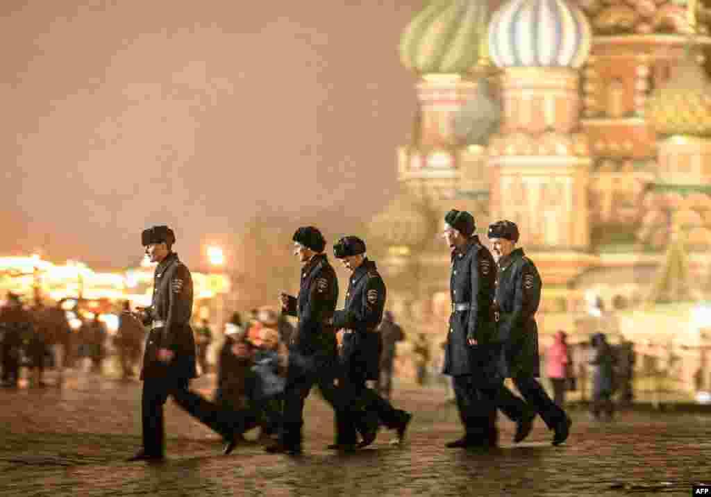 Para kadet militer Rusia berjalan saat hujan salju di depan Katedral St Basil di Lapangan Merah, Moskow, Rusia.