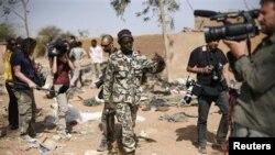Un soldat malien demande aux journalistes de quitter l'endroit où a eu lieu une frappe de l'armée française, à Konna, 688 kms au nord de Bamako, le 26 jan. 2013