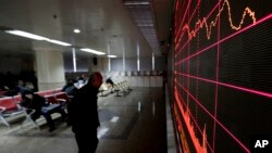 A man looks at an electronic board displaying stock prices at a brokerage house in Beijing, Jan. 26, 2016.