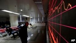 一名男子在北京一个股票交易所里观看电子屏幕显示的股市行情。(2016年1月26日)