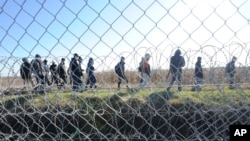 FILE - Migrants walk behind a temporary protective fence at the border between Hungary and Serbia near Morahalom, southeast of Budapest, Hungary, Feb. 22, 2016. Germany last year declared several Balkan nations, whose citizens are barely ever granted asylum, safe countries.