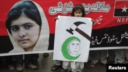 A girl holds a placard next to an image of schoolgirl Malala Yousufzai, who was shot on October 9 by the Taliban, during a rally organized by National Students Federation (NSF) in Lahore October 15, 2012.