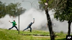 Protesters caught in teargas, hurl stones at police, unseen, during violent clashes in Sasolburg, South Africa, January 22 2013.