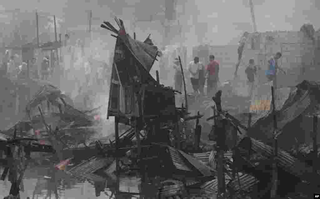 Residents return to their still smoldering homes after a fire broke out at a slum area in Pasay, south of Manila, Philippines. Pasay City Fire Marshall Major Douglas Guiyab said about 250 houses were gutted in the area and the cause of the fire is still being determined.