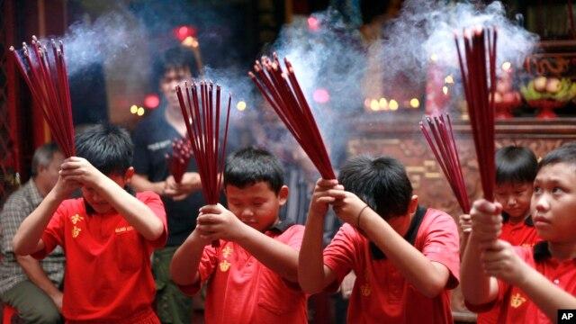 Anak-anak etnis Tionghoa Indonesia  berdoa di sebuah Klenteng di Jakarta (7/1).