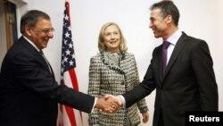 El secretario de defensa, Leon Panetta, y el secretario general de la OTAN, Anders Rasmussen, se saludan, mientras observa la secretaria de Estado, Hillary Clinton.