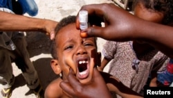 FILE - A health worker drops anti-polio vaccine into the mouth of a Somali child in Mogadishu September 10, 2006.