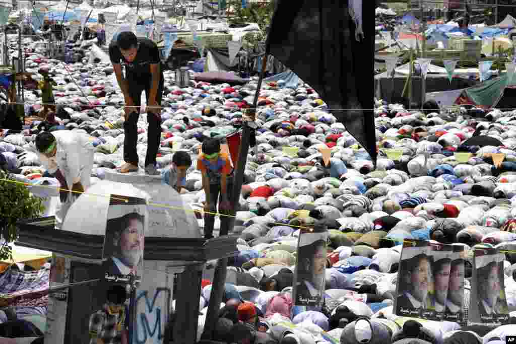 Supporters of Egypt's ousted President Mohammed Morsi offer their Friday prayer where protesters have installed their camp and held their daily rally, at Nasr City, Cairo, Egypt, July 19, 2013.