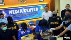 Dua tersangka penyelundupan 4 Kg shabu menunjukkan bagaimana shabu diselundupkan di dalam tas perempuan, di Bandara Yogyakarta, 28/12/2014.