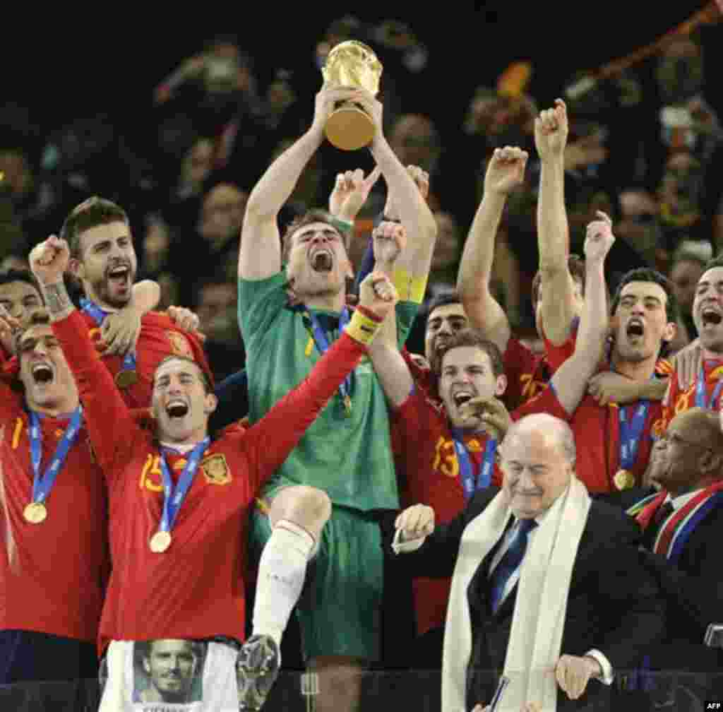 Spain goalkeeper Iker Casillas, center, holds up the World Cup trophy as he and other team members celebrate, as South African President Jacob Zuma, front right, and FIFA president Sepp Blatter, second from right in front, look on during the World Cup fin