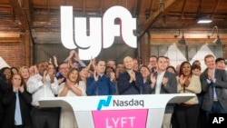 Lyft co-founders John Zimmer, center left, and Logan Green, center right, attend Lyft's IPO event in Los Angeles, California, March 29, 2019.