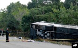 The lifeless body of a passenger lies next to an overturned bus in Mahahual, Quintana Roo state, Mexico, Tuesday, Dec. 19, 2017.