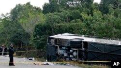 Le corps sans vie d'un passager à côté du bus qui s'est renversé à Mahahual au Mexique, mardi 19 décembre 2017.