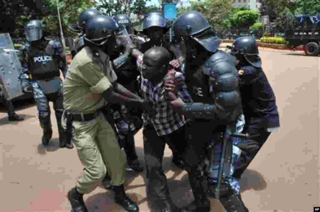 Uganda police detain a supporter of Uganda's top opposition leader Kizza Besigye outside the court in Kampala, Uganda, Wednesday, March 28, 2012. Besigye and his co-accused pleaded not guilty Wednesday and were freed on bail, from charges of convening an