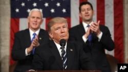 도널드 트럼프(가운데) 대통령이 28일 첫 상· 하원 합동연설을 진행하는 도중 마이크 펜스(왼쪽) 부통령과 폴 라이언 하원의장이 기립박수하고 있다.
