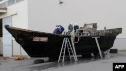 지난 2015년 11월 일본 서부 후쿠이현 후쿠이항에서 해안경비대원들이 북한에서 떠내려온 것으로 보이는 목조선을 조사하고 있다. (자료사진)
