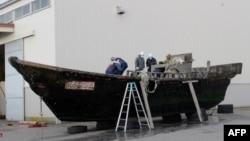 지난 2015년 11월 일본 서부 후쿠이현 후쿠이항에서 해안경비대원들이 북한에서 떠내려온 것으로 보이는 목조선을 조사하고 있다.