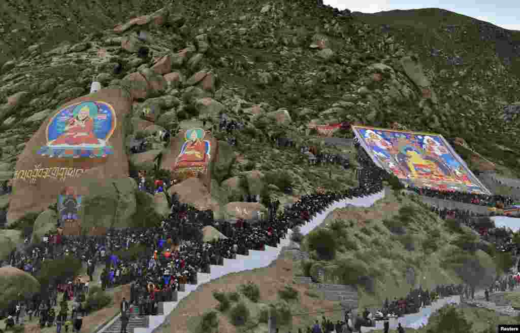 Tibetan Buddhists and tourists view a giant thangka, a religious silk embroidery or painting displaying the Buddha portrait, during the Shoton Festival at Drepung Monastery in Lhasa, Tibet Autonomous Region.
