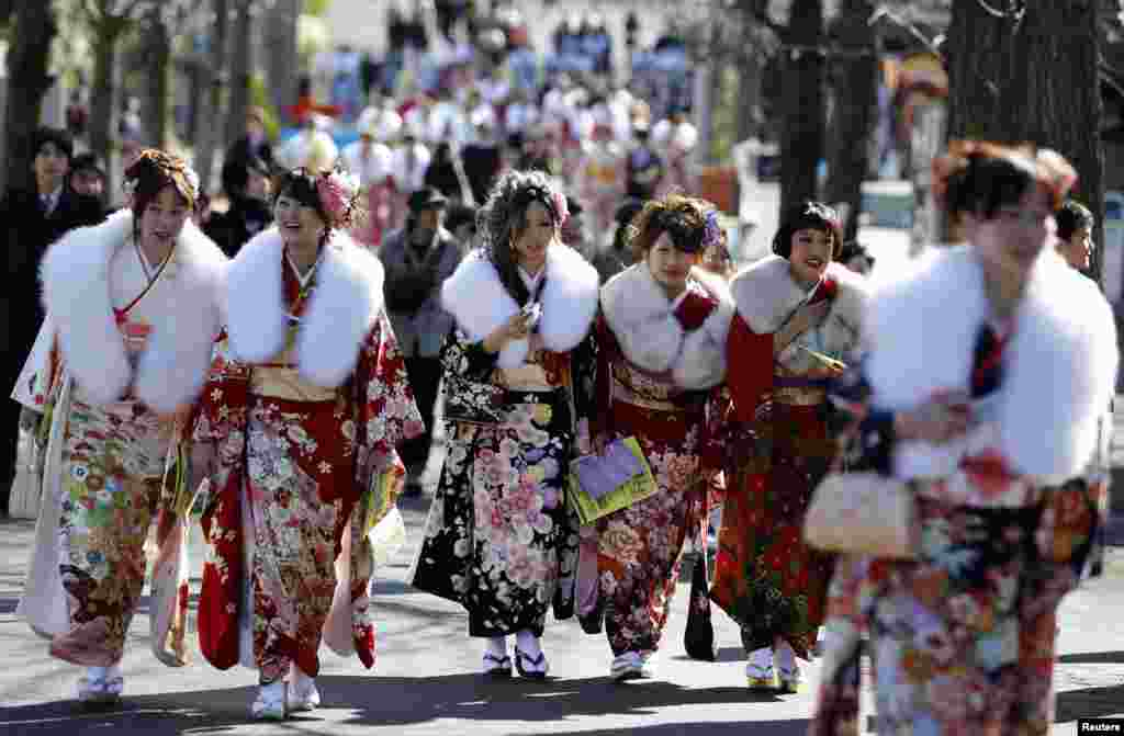 Japanese women in kimonos attend a ceremony celebrating Coming of Age Day at an amusement park in Tokyo.