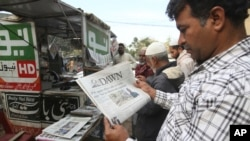 People read newspapers carrying headlines about India Pakistan tensions, in Karachi, Pakistan, Thursday, Feb. 28, 2019.