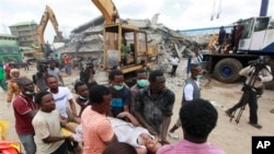 FILE-Rescue workers carry a survivor from the rubble of a collapsed building belonging to the Synagogue Church of All Nations in Lagos, Nigeria, Sept. 13, 2014.