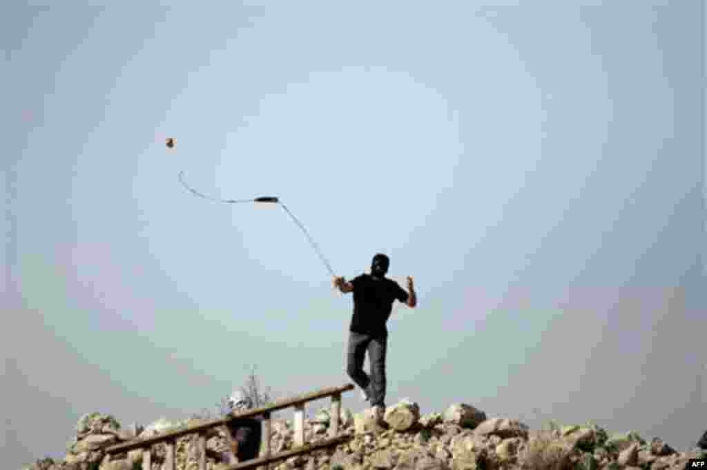 January 14: A Palestinian protester uses a slignshot to hurl a stone at Israeli troops, during a protest against Israel's separation barrier in the West Bank village of Nilin near Ramallah. (AP Photo/Majdi Mohammed)