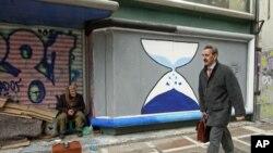 一个希腊擦鞋人3月12日坐在雅典市中心已经关张的商铺前看行人路过