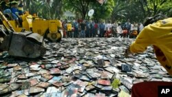 A Manila City Hall employee throws pirated DVDs (Digital Video Discs) onto the path of the steamrollers as they are destroyed, file photo.