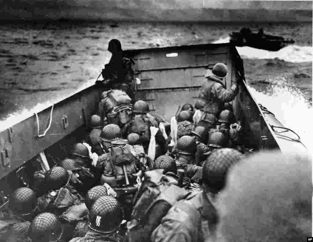 Allied troops crouch behind the bulwarks of a landing craft as it nears Omaha Beach during the D-Day invasion, Normandy, France, June 6, 1944.
