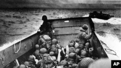 Allied troops crouch behind the bulwarks of a landing craft as it nears Omaha Beach during a landing in Normandy, France, June 6, 1944.