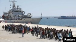 Migrants are disembarked from the Italian navy ship Vega in the Sicilian harbor of Augusta, southern Italy, May 4, 2015.