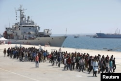 FILE - Migrants are disembarked from the Italian navy ship 'Vega' in the Sicilian harbour of Augusta, southern Italy, May 4, 2015.