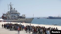 FILE - Migrants are disembarked from the Italian navy ship Vega in the Sicilian harbor of Augusta, southern Italy, May 4, 2015.