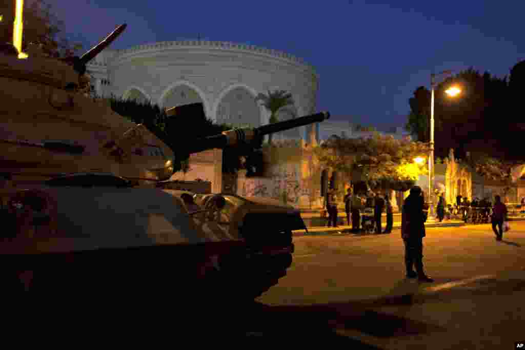 An army soldier guards his tank in front the presidential palace in Cairo, Egypt, December 12, 2012.