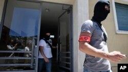Polisi khusus Perancis yang mengenakan topeng tampak meninggalkan gedung apartemen di mana tersangka penyerang, Mohamed Lahouaiej Bouhlel, tinggal di kota Nice, Sabtu (16/7).