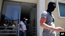 Des policiers français en cagoule emportent des documents lors d'une perquisition au domicile de Mohamed Lahouaiej Bouhlel, l'auteur présumé de l'attaque de Nice, dans sud de la France, 16 juillet 2016. (AP Photo / Luca Bruno)