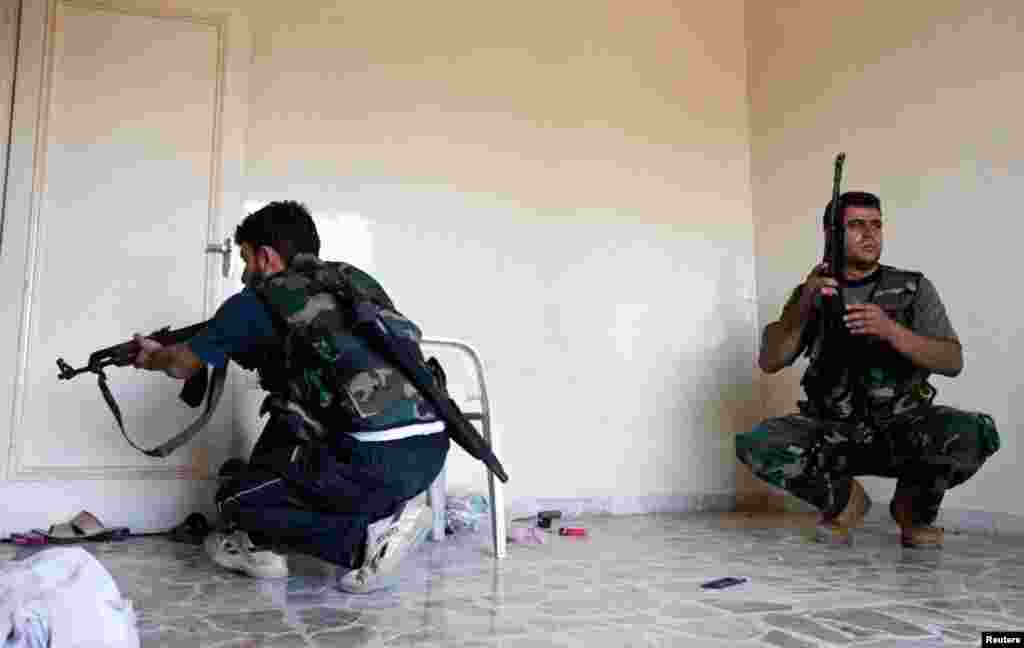 Members of the Free Syrian Army take cover inside a house during clashes with Syrian army soldiers in Aleppo's Saif al-Dawla district, August 22, 2012.