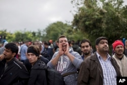 FILE - A man shouts while people wait to clear a police line as they entered into Croatia from Serbia, in Babska, Croatia, Sept. 25, 2015.