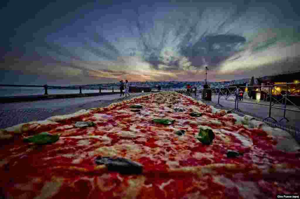 Pizza Neapolitan sepanjang dua kilometer memecahkan rekor dunia Guinness sebagai pizza terpanjang di dunia, dibuat di kota Naples, Italia.