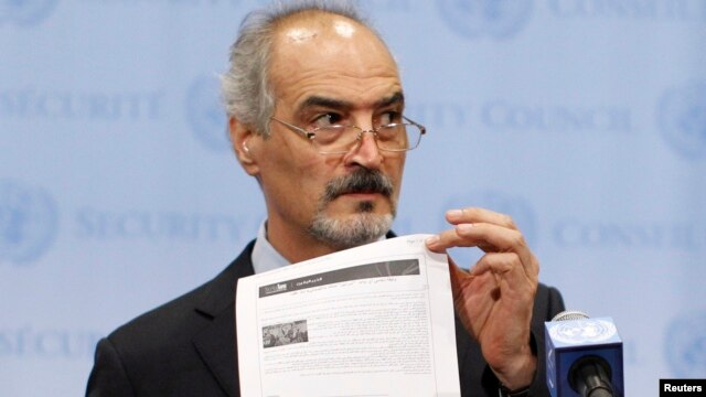 Syrian U.N. Ambassador Bashar Ja'afari shows a document to reporters at the United Nations Headquarters in New York, Sept. 12, 2013.