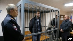 Police officers guards a cage with Greenpeace activist Ruslan Yakushev of Ukraine, Sept. 26, 2013.